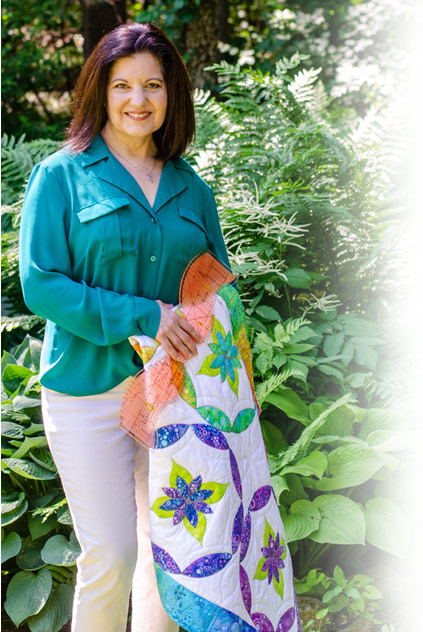 Sue Pelland in the garden with one of her quilts